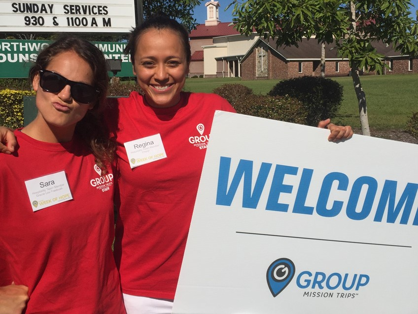 Employees holding welcome sign