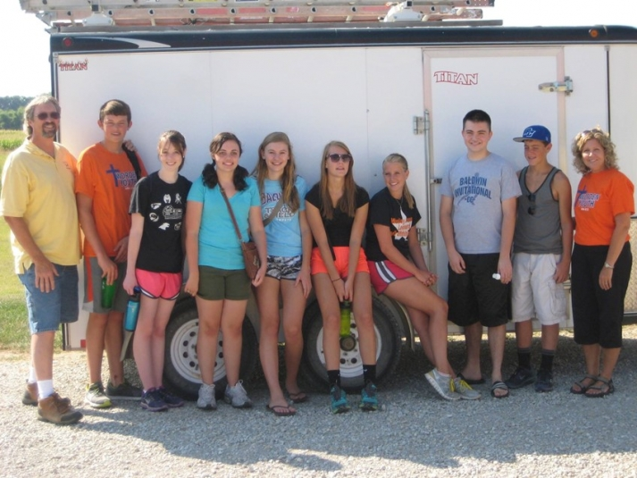 Youth group standing by trailer
