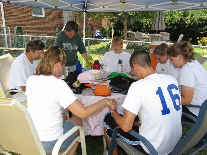 Youth praying around the table with those in need